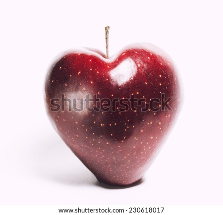 attractive teasing red apple in the shape of heart close up isolated on white - stock photo