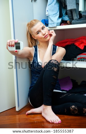 attractive teen girl making selfie with mobile phone in her room in front of open closet - stock photo