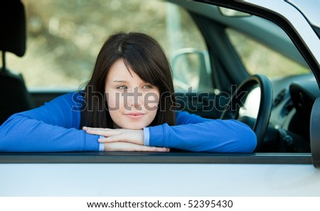 Attractive teen girl smiling at the camera sitting in her car outdoor - stock photo