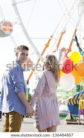Attractive teenage couple in an amusement park with rides, holding balloons up in the air and turning around to look at the camera while holding hands. - stock photo
