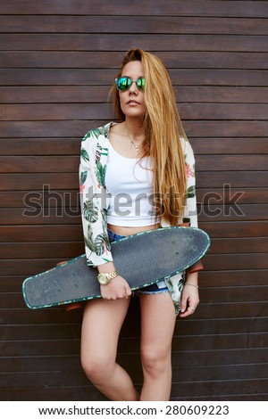 Attractive teenage girl in sunglasses holding her skateboard while standing against wooden wall background, casually-dressed female hipster with beautiful figure posing with long-board in summer  - stock photo