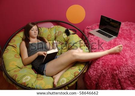 Attractive teenage girl reads book in her room. - stock photo