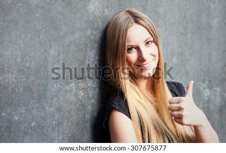 Attractive teenage girl showing thumbs up - stock photo