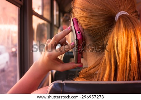 Attractive teenage girl with red orange hair talking over her pink smartphone in public transport looking through window in a sunsetting light - rear view - stock photo