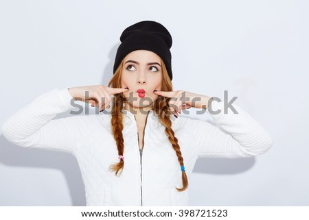 Attractive teenage red-haired girl with long hair wearing white shirt and black hat, stylish haircut and makeup, red lips, portrait, emotions. - stock photo