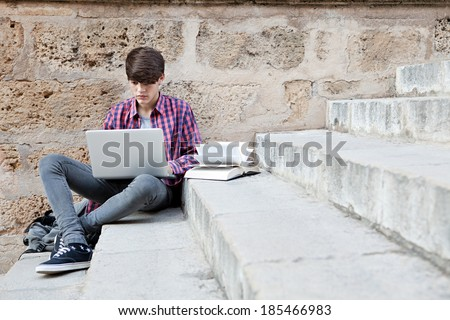 Attractive teenager boy sitting on a college campus with school books and a laptop computer against an old stone building wall doing his homework. Education technology lifestyle. - stock photo