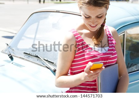 Attractive teenager girl using her smartphone cell phone while sitting on a classic car in a city with a sunny sky, typing a message and smiling. - stock photo