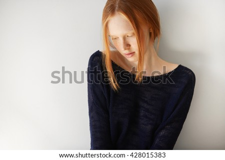 Attractive teenager model wearing stylish black top looking down with shy and dreamy expression on her face. Headshot of coy redhead student girl with clean healthy freckled skin and no make up - stock photo