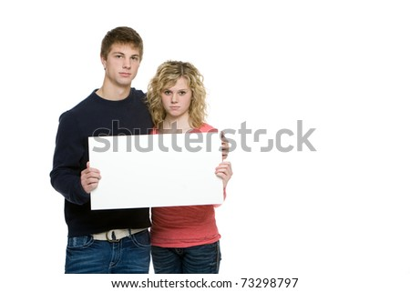 Attractive teenagers holding blank sign isolated on white - stock photo