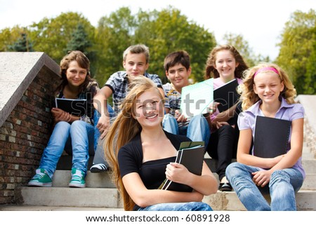 Attractive teenagers with books laughing - stock photo