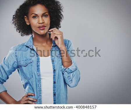 Attractive thoughtful young African American woman in a trendy blue denim shirt standing with her hand raised to her face looking at the camera with a pensive expression, on grey with copy space - stock photo
