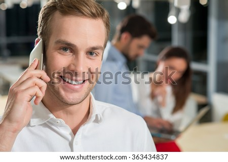 Attractive three colleagues are discussing a new project in office. The businessman is talking on the mobile phone and smiling. His team is standing and using a laptop on background - stock photo