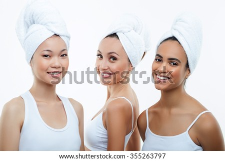 Attractive three girls are relaxing at spa. They are standing with white towels over their heads. The ladies are looking at camera and smiling. Isolated - stock photo