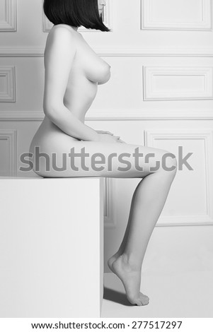 Attractive topless woman sitting on white table.Monochrome portrait of sexy naked girl with big breasts - stock photo