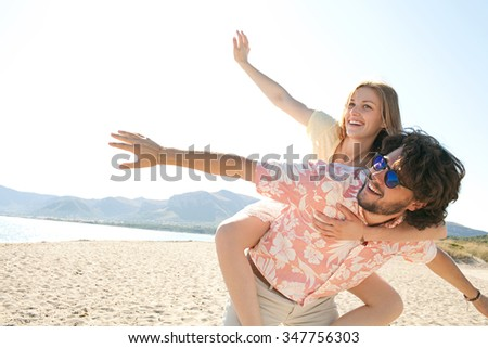 Attractive tourist couple on holiday, with man carrying girl in piggyback on sandy beach destination with sunny blue sky, outdoors space. Romance and dynamic honeymoon fun lifestyle, summer exterior. - stock photo