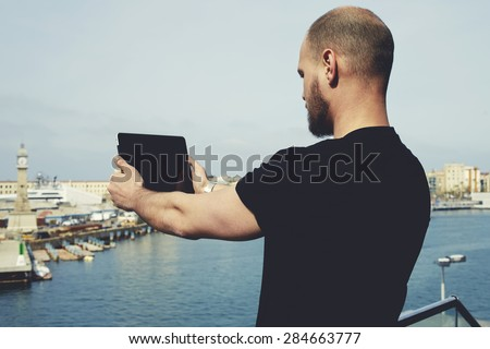 Attractive tourist with digital tablet camera taking picture of beautiful city from viewpoint, young handsome man photographing marina port city with touch pad,male enjoying vacation journey in summer - stock photo