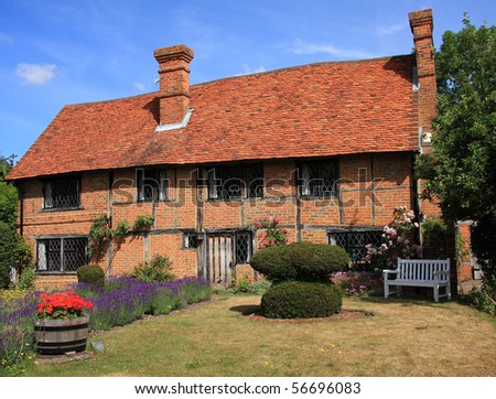 Attractive traditional English period cottage of brick and timber construction complete with lavender flower garden - stock photo