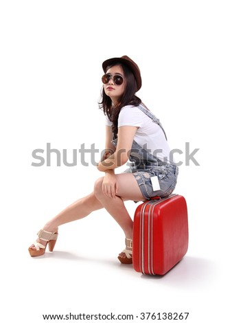 Attractive traveler woman in vintage outfit sitting on a red suitcase, isolated on white background - stock photo