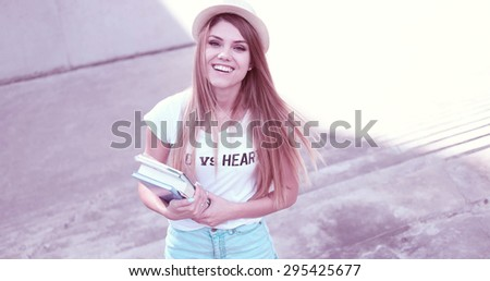 Attractive trendy young female student holding books happy - stock photo