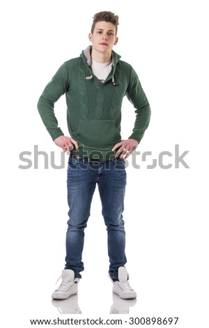 Attractive trendy young man wearing jeans and green knitted sweater, isolated on white background, looking at camera - stock photo