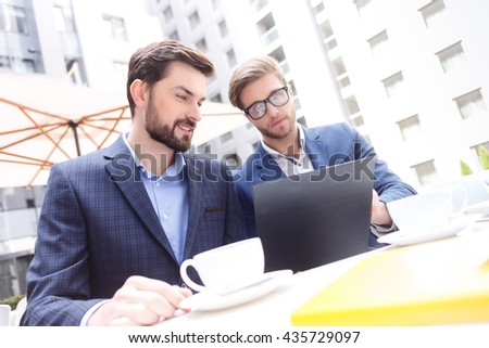 Attractive two businessmen are working in cooperation - stock photo