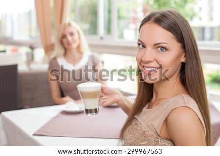 Attractive two women are sitting at the table in cafe. They are drinking latte with enjoyment. Focus on brunette girl. She is holding the cup and smiling - stock photo