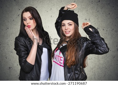 Attractive. Two young girl friends having fun together. Brunette smiling (duck face), hand next to her lips. Blonde making happy face and jumping. Inside - stock photo