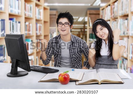 Attractive two young high school students studying together in the library and celebrate their winning - stock photo