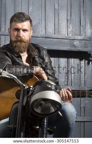 Attractive unshaven musical man with beard and handlebar moustache in leather jacket sitting on motorcycle with acoustic guitar in garage on wooden wall background copyspace, vertical picture - stock photo