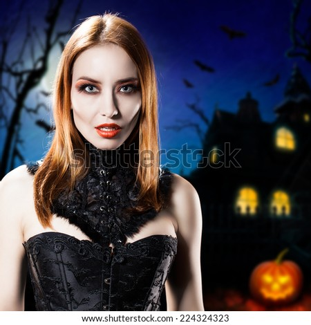 attractive vampire in front of a halloween house  - stock photo
