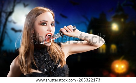 attractive vampire with a bloody knife - stock photo
