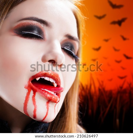attractive vampire with bloody mouth - stock photo