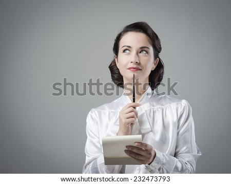 Attractive vintage secretary taking notes with notepad and pen - stock photo