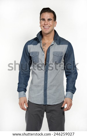 Attractive white caucasian male model laughing while wearing a jean shirt and gray pants posing in a studio on a white background while looking at the camera. - stock photo