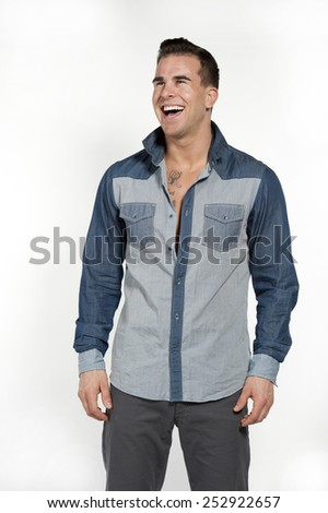 Attractive white caucasian male model laughing while wearing a jean shirt and gray pants posing in a studio on a white background while looking to the left. - stock photo