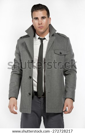 Attractive white male wearing a fitted white shirt and gray pants with a black belt and gray jacket while posing in a studio setting on a white background and looking at the camera. - stock photo