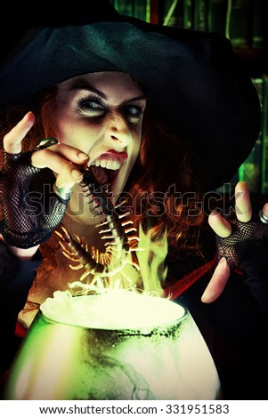 Attractive witch in the wizarding lair. Fairytales. Halloween. - stock photo