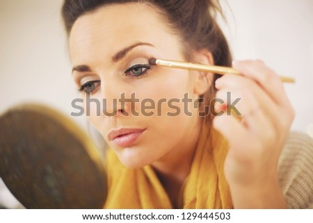 Attractive woman applying makeup while looking at the mirror - stock photo
