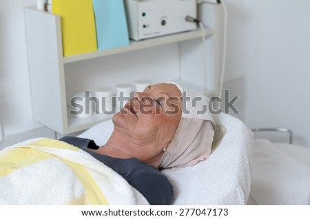attractive woman at beauty center receiving facial treatment - stock photo