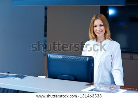 attractive woman at reception desk looking at camera - stock photo