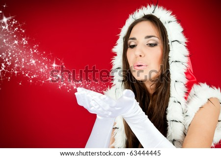 attractive woman blowing snow from her hands - stock photo