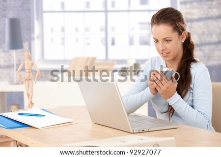 Attractive woman browsing internet at home, drinking tea, looking at screen.? - stock photo
