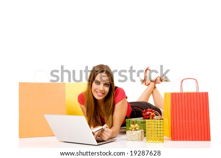 Attractive woman buying over internet hold credit card in hand with many colorful bags and gift boxes. - stock photo