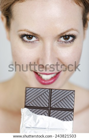 Attractive woman choosing between chocolate and a fresh apple. - stock photo