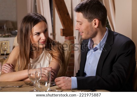 Attractive woman coquetting her friend during meeting in restaurant - stock photo