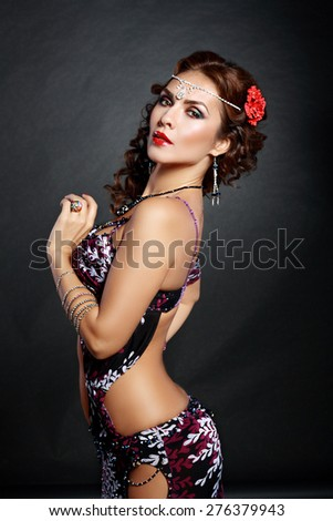 attractive woman dancing belly dance over black background - stock photo