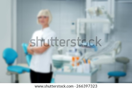 attractive woman dentist standing in her office with her equipment , blurred for presentation , abstract background - stock photo