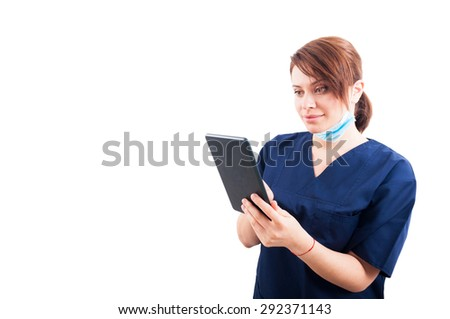Attractive woman doctor using wireless tablet on white copyspace - stock photo