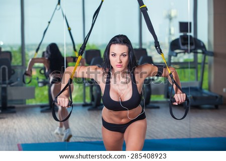 attractive woman does crossfit push ups with trx fitness straps in the gym's studio - stock photo