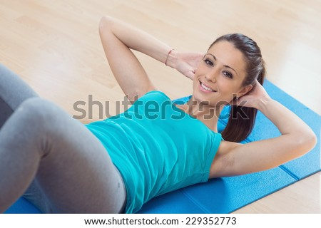 Attractive woman doing abs workout at gym for muscle toning and flat stomach. - stock photo